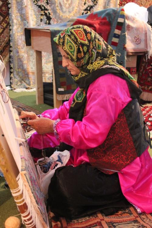 Iranian woman making carpet